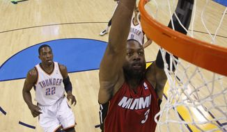 Miami Heat guard Dwyane Wade goes up for a dunk in front of Oklahoma City Thunder forward Jeff Green (left) in the first quarter of Miami's 108-103 win Sunday in Oklahoma City. (Associated Press)