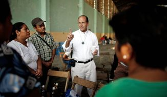 The Rev. Alejandro Solalinde talks with migrants at a shelter in Chahuites, in southern Mexico's Oaxaca state, on Jan. 8. He warns migrants of their risk of being abducted and perhaps killed by the Zetas-linked kidnappers. (Associated Press)