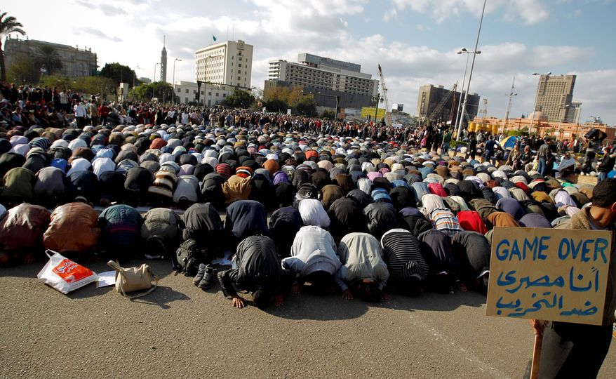 "Anti-government protesters pray Monday at Tahrir Square in Cairo. A coalition of opposition groups called for a million people to take to Cairo's streets Tuesday. The Arabic on the sign reads ""I'm Egyptian, anti-destruction."" (Associated Press)"