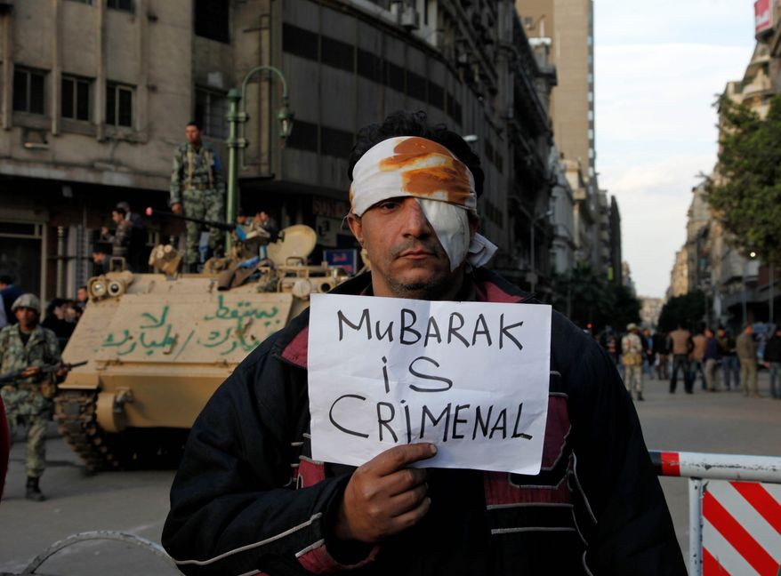 A wounded demonstrator carries a poster in Cairo on Monday. A coalition of protesters hopes Tuesday to increase the pressure on President Hosni Mubarak to resign. (Associated Press)