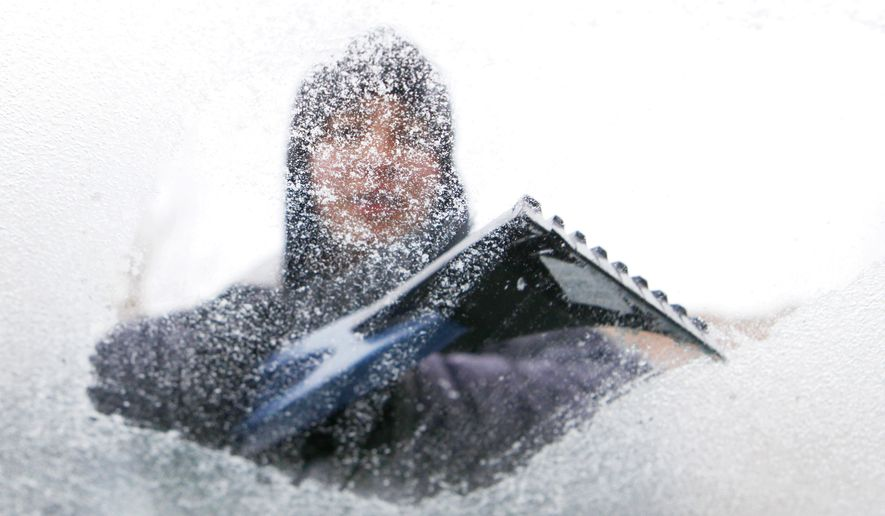 Lydia Vasquez scrapes ice from the windshield of her car in Denver on Monday, Jan. 31, 2011. A front moved through Colorado early Monday morning, bringing with it freezing rain, snow and cold. (AP Photo/Ed Andrieski)