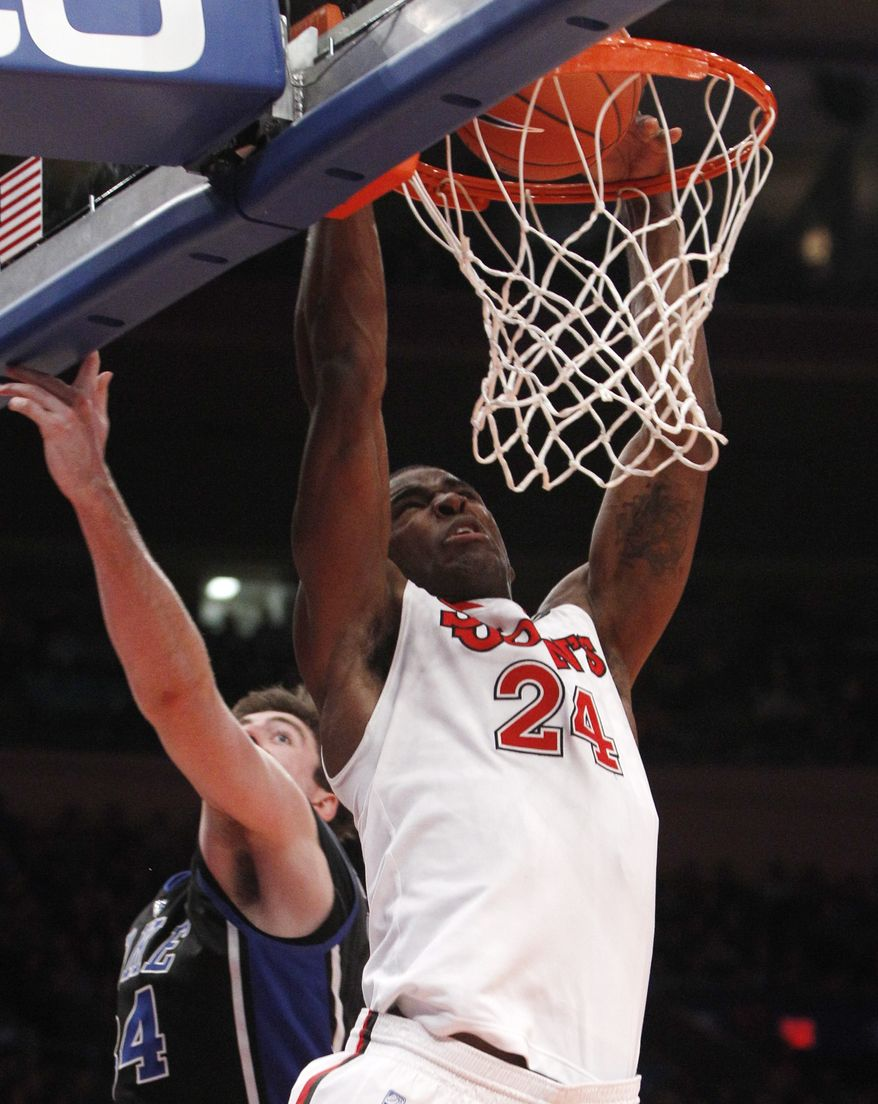 St. John's forward Justin Burrell (24) dunks in front of Duke forward Ryan Kelly in the second half of the Red Storm's upset of the third-ranked Blue Devils, 93-78, on Sunday at Madison Square Garden. (Associated Press)