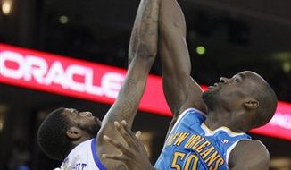 New Orleans Hornets' Emeka Okafor, right, goes up for a shot against Golden State Warriors' Dorell Wright during the first half of an NBA basketball game Wednesday, Jan. 26, 2011, in Oakland, Calif. (AP Photo/Ben Margot)