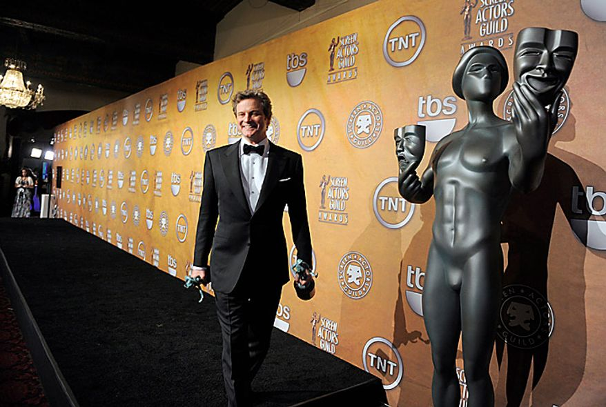 """Colin Firth holds awards for best actor and ensemble for """" The King's Speech"""" at the 17th Annual Screen Actors Guild Awards on Sunday, Jan. 30, 2011, in Los Angeles. (AP Photo/Chris Pizzello)"""
