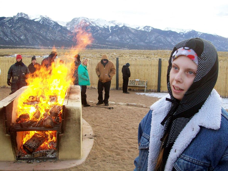 Brandi Ellis, 18, talks to a reporter during the outdoor cremation of her mother, Belinda Ellis, 48, in Crestone, Colo., on Jan. 12. The funeral industry says Crestone is the only place in the U.S. where anyone, regardless of religion, can have a funeral pyre. (Associated Press)