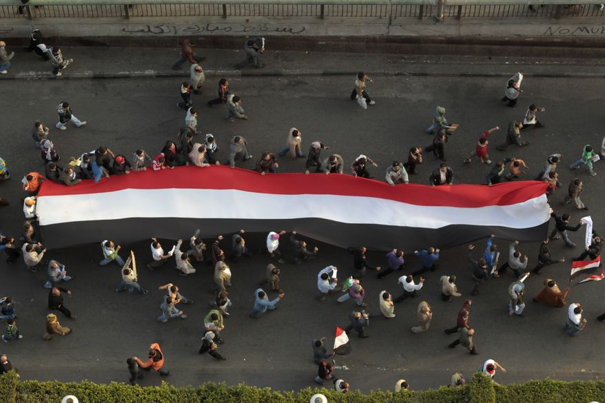 Demonstrators carry a huge flag in Tahrir, or Liberation, Square in Cairo, Egypt, Tuesday, Feb. 1, 2011. More than a quarter-million people flooded into the heart of Cairo Tuesday, filling the city's main square in by far the largest demonstration in a week of unceasing demands for President Hosni Mubarak to leave after nearly 30 years in power. (AP Photo/Lefteris Pitarakis)