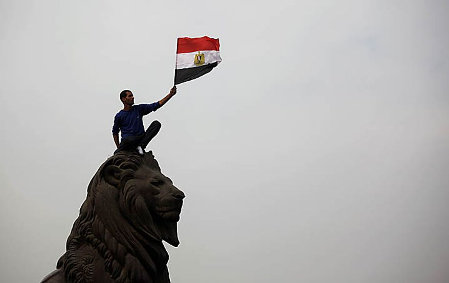 An Egyptian man waves the national flag atop a statue just outside Tahrir, or Liberation, Square in Cairo on Tuesday, Feb. 1, 2011. More than a quarter-million people flooded into the heart of the city, filling the the main square in by far the largest demonstration in a week of unceasing demands for President Hosni Mubarak to leave after nearly 30 years in power. (AP Photo/Emilio Morenatti)