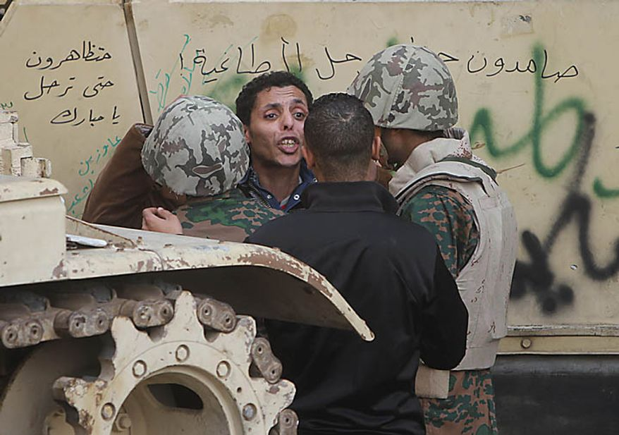 A man is detained for unknown reasons by soldiers just outside Tahrir, or Liberation, Square in Cairo on Tuesday, Feb. 1, 2011. More than a quarter-million people flooded into the heart of Cairo, filling the city's main square in by far the largest demonstration in a week of unceasing demands for President Hosni Mubarak to leave after nearly 30 years in power. (AP Photo/Ahmed Ali)