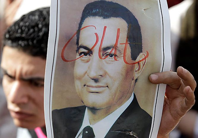 A demonstrator holds up a portrait of Egyptian President Hosni Mubarak in Tahrir, or Liberation, Square in Cairo on Tuesday, Feb. 1, 2011. More than a quarter-million people flooded into the heart of Cairo, filling the city's main square in by far the largest demonstration in a week of unceasing demands for President Hosni Mubarak to leave after nearly 30 years in power. (AP Photo/Ben Curtis)