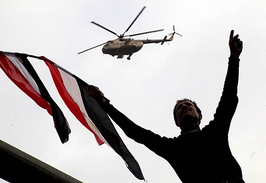 An Egyptian army helicopter patrols above a protester waving an Egyptian flag as crowds gather in Tahrir, or Liberation, Square in Cairo on Tuesday, Feb. 1, 2011. More than a quarter-million people flooded into the heart of Cairo, filling the city's main square in by far the largest demonstration in a week of unceasing demands for President Hosni Mubarak to leave after nearly 30 years in power. (AP Photo/Amr Nabil)