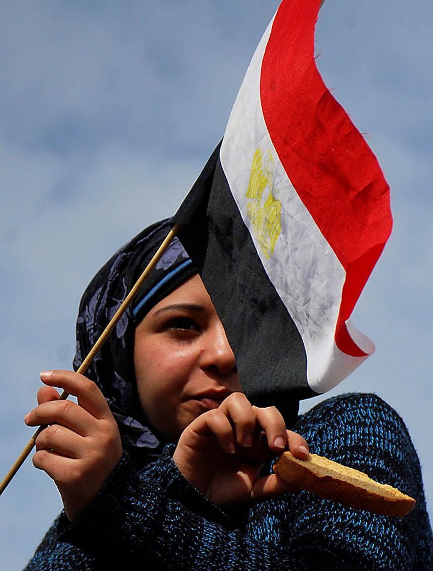 A woman holding an Egyptian flag attends a demonstration in Tahrir, or Liberation, Square in Cairo on Tuesday, Feb. 1, 2011. More than a quarter-million people flooded into the heart of Cairo, filling the city's main square in by far the largest demonstration in a week of unceasing demands for President Hosni Mubarak to leave after nearly 30 years in power. (AP Photo/Mohammed Abu Zaid)