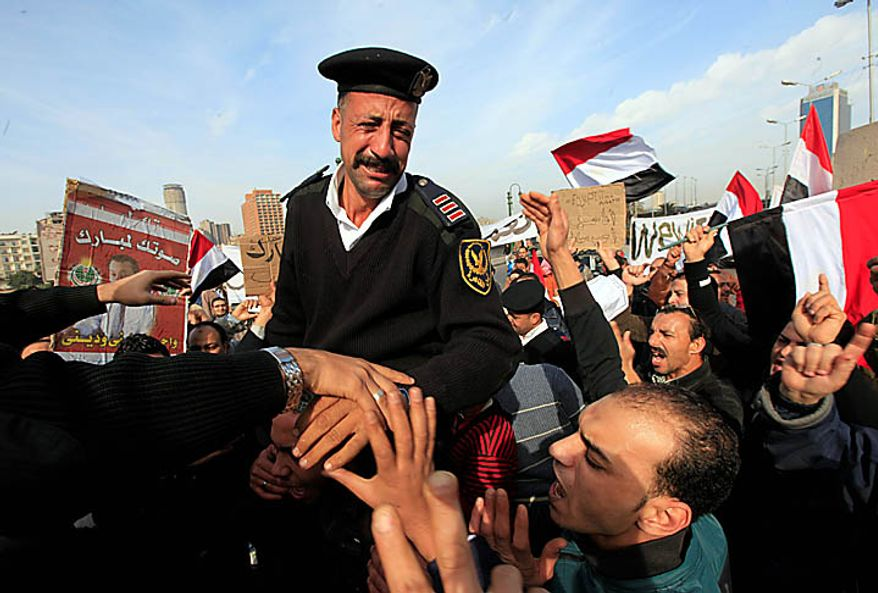 An Egyptian policeman cries as he receives a warm welcome by pro-Mubarak supporters in Cairo on Tuesday, Feb. 1, 2011, three days after the police disappeared from the streets. (AP Photo/Amr Nabil)
