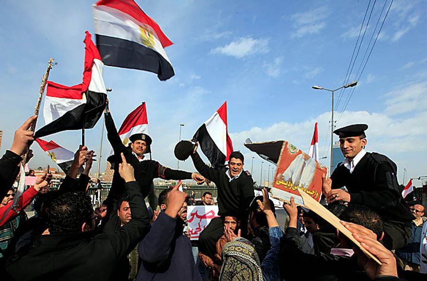 Egyptian policemen are carried by pro-Mubarak supporters as they received a warm welcome in Cairo on Tuesday, Feb. 1, 2011, three days after the police disappeared from the streets. (AP Photo/Amr Nabil)