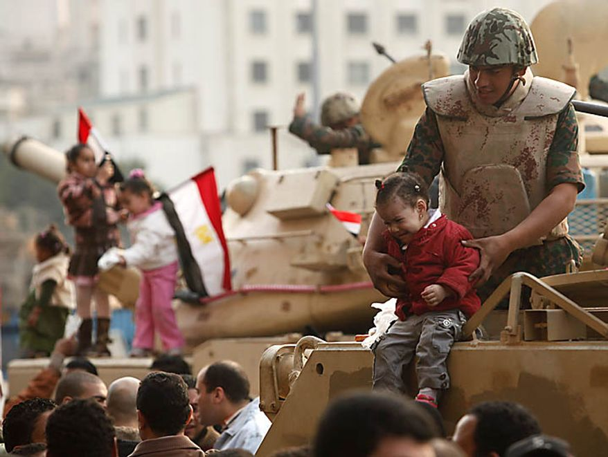 A soldier holds a crying girl on his armored vehicle just outside Tahrir, or Liberation, Square in Cairo on Tuesday, Feb. 1, 2011. More than a quarter-million people flooded into the heart of Cairo, filling the city's main square in by far the largest demonstration in a week of unceasing demands for President Hosni Mubarak to leave after nearly 30 years in power. (AP Photo/Victoria Hazou)