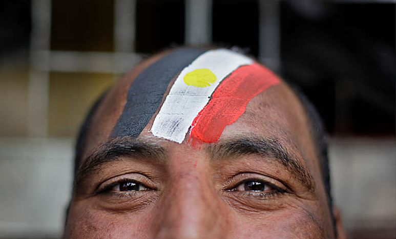 An anti-government protester wears face paint in the colors of the Egyptian flag during the continuing demonstrations in Tahrir Square in downtown Cairo on Tuesday, Feb. 1, 2011. More than a quarter-million people flooded into the heart of Cairo, filling the city's main square in by far the largest demonstration in a week of unceasing demands for President Hosni Mubarak to leave after nearly 30 years in power. (AP Photo/Ben Curtis)