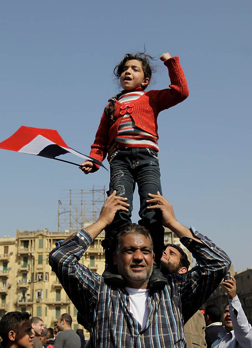 A girl standing on a man's shoulders reacts during a demonstration in Tahrir, or Liberation, Square in Cairo on Tuesday, Feb. 1, 2011. More than a quarter-million people flooded into the heart of Cairo Tuesday, filling the city's main square in by far the largest demonstration in a week of unceasing demands for President Hosni Mubarak to leave after nearly 30 years in power. (AP Photo/Ben Curtis)