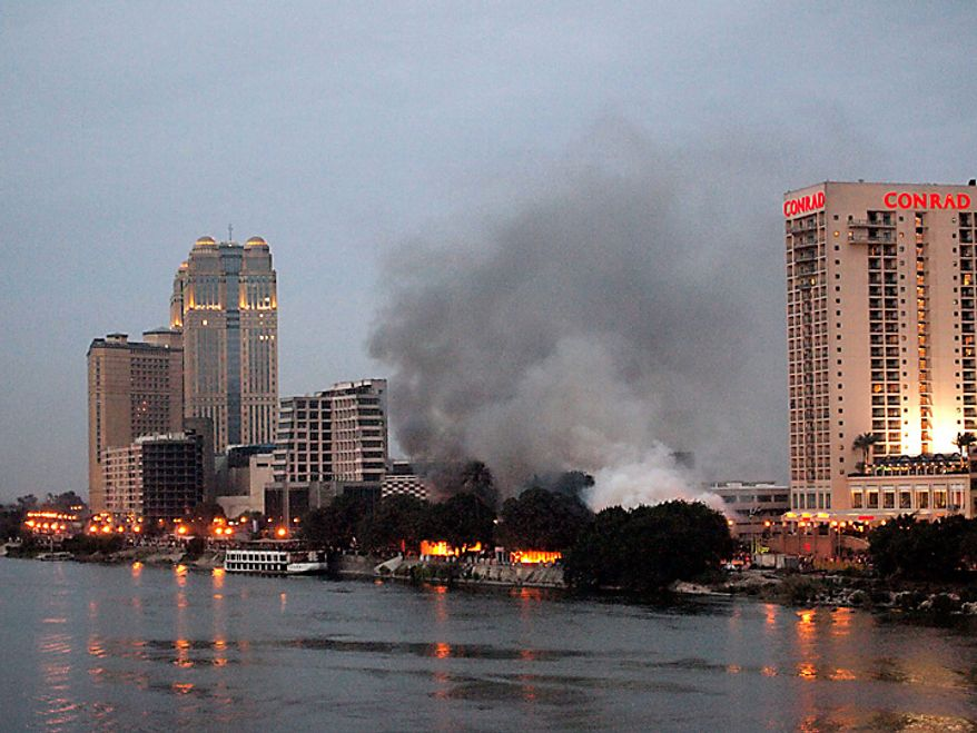 Smoke rises from a restaurant and nightclub set ablaze near the Conrad hotel (right) on the banks of the River Nile in Cairo on Friday, Jan. 28, 2011. Egyptian protesters began gathering in Cairo for a march aimed at drawing a million people onto the streets and forcing President Hosni Mubarak from power. (Bloomberg/Digby Lidstone)