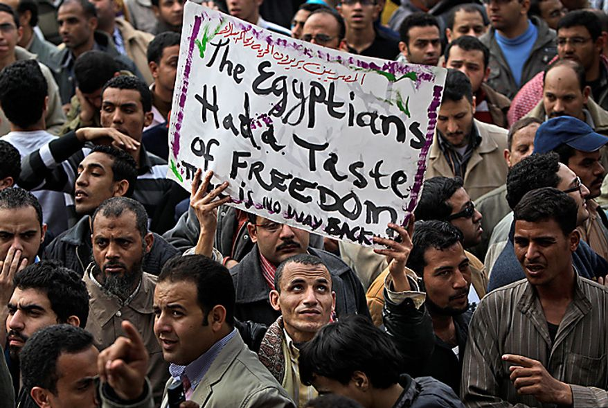 "An anti-government protester holds a banner reading: ""The Egyptians had a taste of freedom. There is no way back,"" during the continuing demonstration in Tahrir Square in downtown Cairo on Tuesday, Feb. 1, 2011. More than a quarter-million people flooded into the heart of Cairo, filling the city's main square in by far the largest demonstration in a week of unceasing demands for President Hosni Mubarak to leave after nearly 30 years in power. (AP Photo/Ben Curtis)"