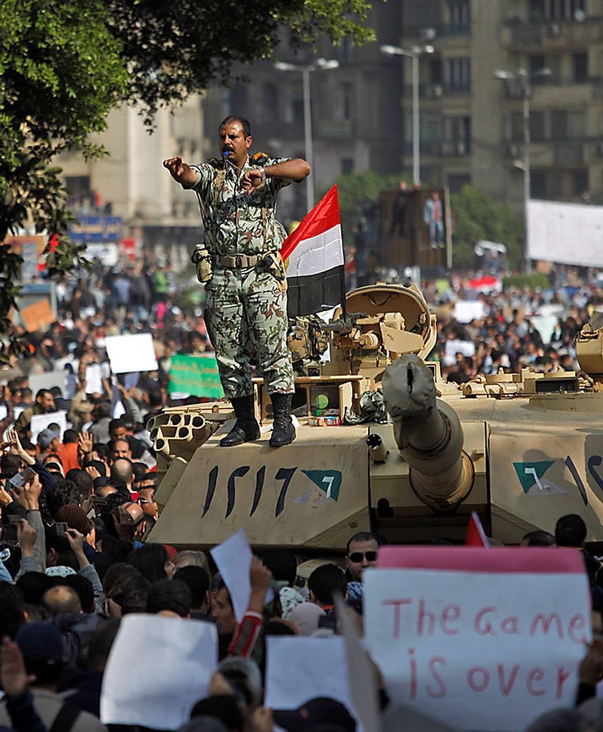 An Egyptian army lieutenant colonel stands on top of a tank as demonstrators arrive in Tahrir, or Liberation, Square in Cairo on Tuesday, Feb. 1, 2011. More than a quarter-million people flooded into the heart of Cairo, filling the city's main square in by far the largest demonstration in a week of unceasing demands for President Hosni Mubarak to leave after nearly 30 years in power. (AP Photo/Emilio Morenatti)