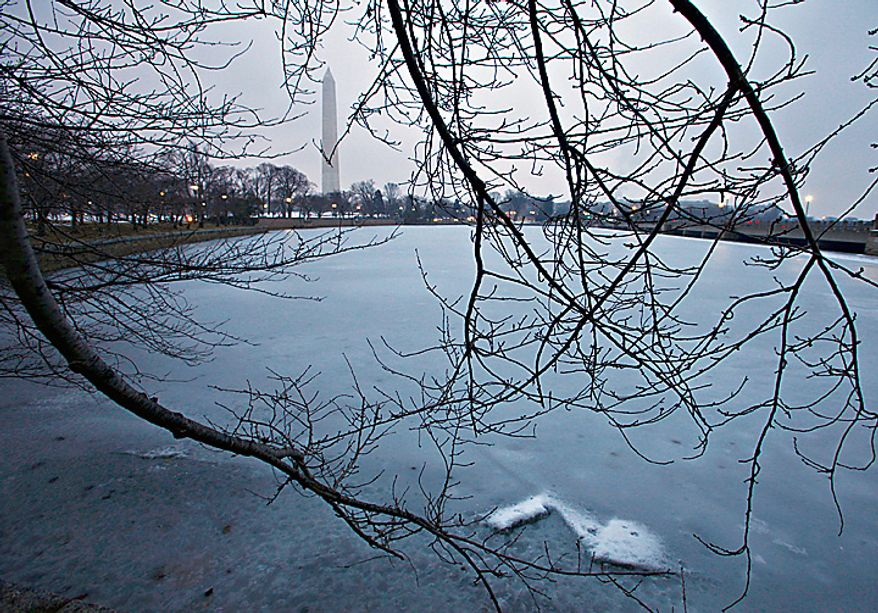 A freezing mist settles over Washington at dawn on Tuesday, Feb. 2, 2011, as icy winter weather advances toward the nation's capital. The Washington Monument is seen in the distance amid the cherry trees bordering the Tidal Basin. (AP Photo/J. Scott Applewhite)