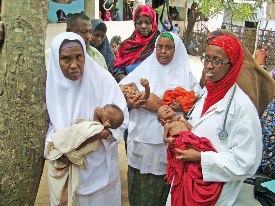 Dr. Amina Adan Mohamed (right) holds one of 37 malnourished infants awaiting treatment at her mother's hospital in Afgoye, Somalia. Dr. Hawa Abdi and her daughters are known throughout Somalia as healers and protectors who don't distinguish among clans, religions or political creeds. (Associated Press)