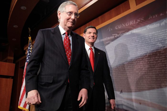 Sens. Mitch McConnell (left), Kentucky Republican, and John Barrasso, Wyoming Republican, depart after speaking to reporters about repealing the health care law at the Capitol on Wednesday. A party-line