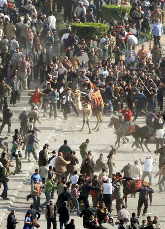 CONFRONTATION: Pro-government demonstrators (bottom), some on horses and camels and armed with sticks, clash Wednesday with anti-government protesters (top) in Cairo's Tahrir Square. On Wednesday, about 200 Americans were flown out of turmoil-racked Egypt. (Associated Press)