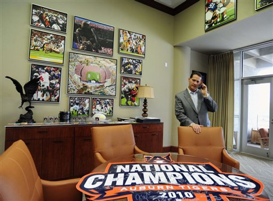 Auburn coach Gene Chizik talks on the phone with quarterback Kiehl Frazier, a recruit from Shiloh Christian High School in Springdale Ark., on Wednesday, Feb. 2, 2011, in Auburn, Ala., after Frazier sent in his paperwork to play NCAA college football and attend Auburn on national signing day.(AP Photo/Todd J. Van Emst)