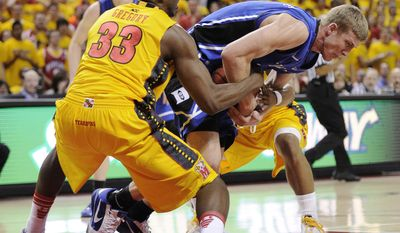 Maryland forward Dino Gregory (33) battles for the ball against Duke forward Mason Plumlee, center, during the first half of an NCAA college basketball game Wednesday, Feb. 2, 2011, in College Park, Md. (AP Photo/Nick Wass)