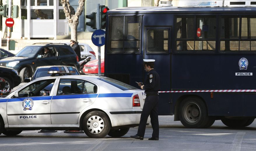 A police car blocks the road that connects to the Justice Ministry, background, after a control explosion in Athens, Wednesday, Feb. 2, 2011. Greek police destroyed a letter bomb sent to the Justice Ministry, and warned other state offices and ministries to watch out for more potentially booby-trapped packages, fearing a repetition of a spate of such bombings in November. (AP Photo/Thanassis Stavrakis)
