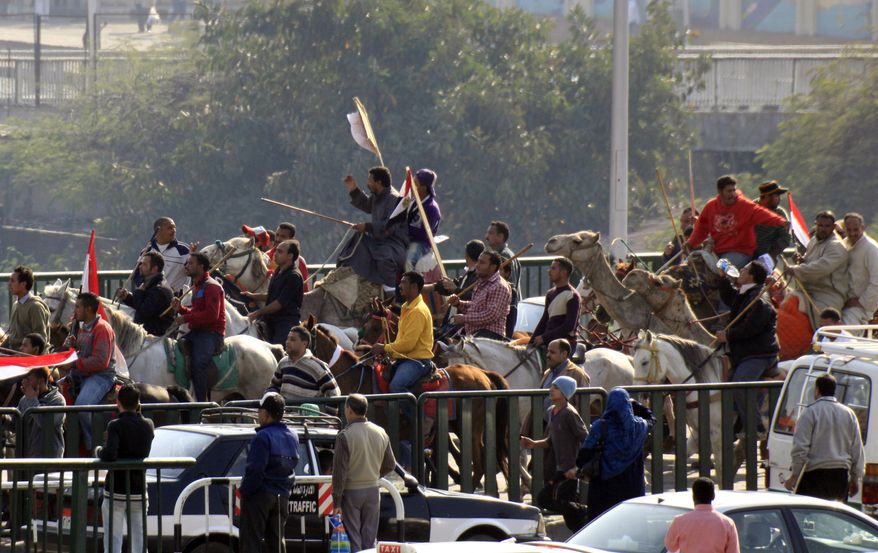 Supporters of Egyptian President Hosni Mubarak, including some riding horses and camels and wielding whips, march toward anti-Mubarak protesters in Cairo on Wednesday, Feb. 2, 2011. (AP Photo/Amr Nabil)