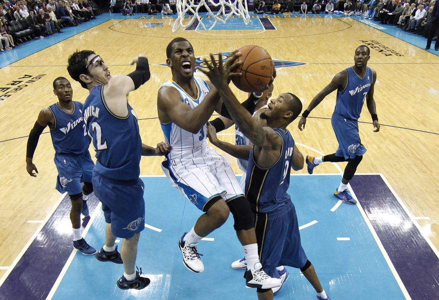 New Orleans Hornets point guard Chris Paul, center, shoots over Washington Wizards point guard John Wall, from left, guard Kirk Hinrich, forward Rashard Lewis and forward Andray Blatche in the second half of an NBA basketball game in New Orleans, Tuesday, Feb. 1, 2011. Paul contributed 15 points and 9 assists in New Orleans' 97-89 win over Washington. (AP Photo/Patrick Semansky)