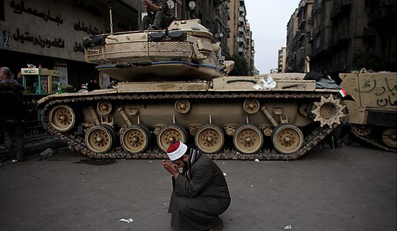 An Egyptian Muslim cleric cries in front of on army tank in Tahrir, or Liberation square, in Cairo Wednesday, Feb. 2, 2011. Several thousand supporters of President Hosni Mubarak, including some riding horses and camels and wielding whips, clashed with anti-government protesters Wednesday as Egypt's upheaval took a dangerous new turn. (AP Photo/Tara Todras-Whitehill)