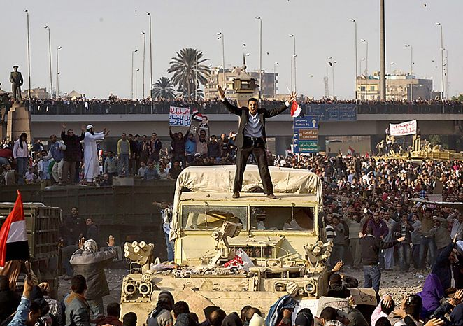 A demonstrator atop a military vehicle tries to calm the crowd, as pro-government demonstrators clash with anti-government protesters during a demonstration in Cairo, Egypt, Wednesday, Feb.2, 2011. Several thousand supporters of President Hosni Mubarak, including some riding horses and camels and wielding whips, clashed with anti-g