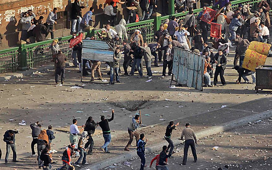 Pro-government demonstrators, below, clash with anti-government demonstrators, above, opposite the Egyptian Museum in Cairo, Egypt, Wednesday, Feb. 2, 2011. (AP Photo/Ben Curtis)