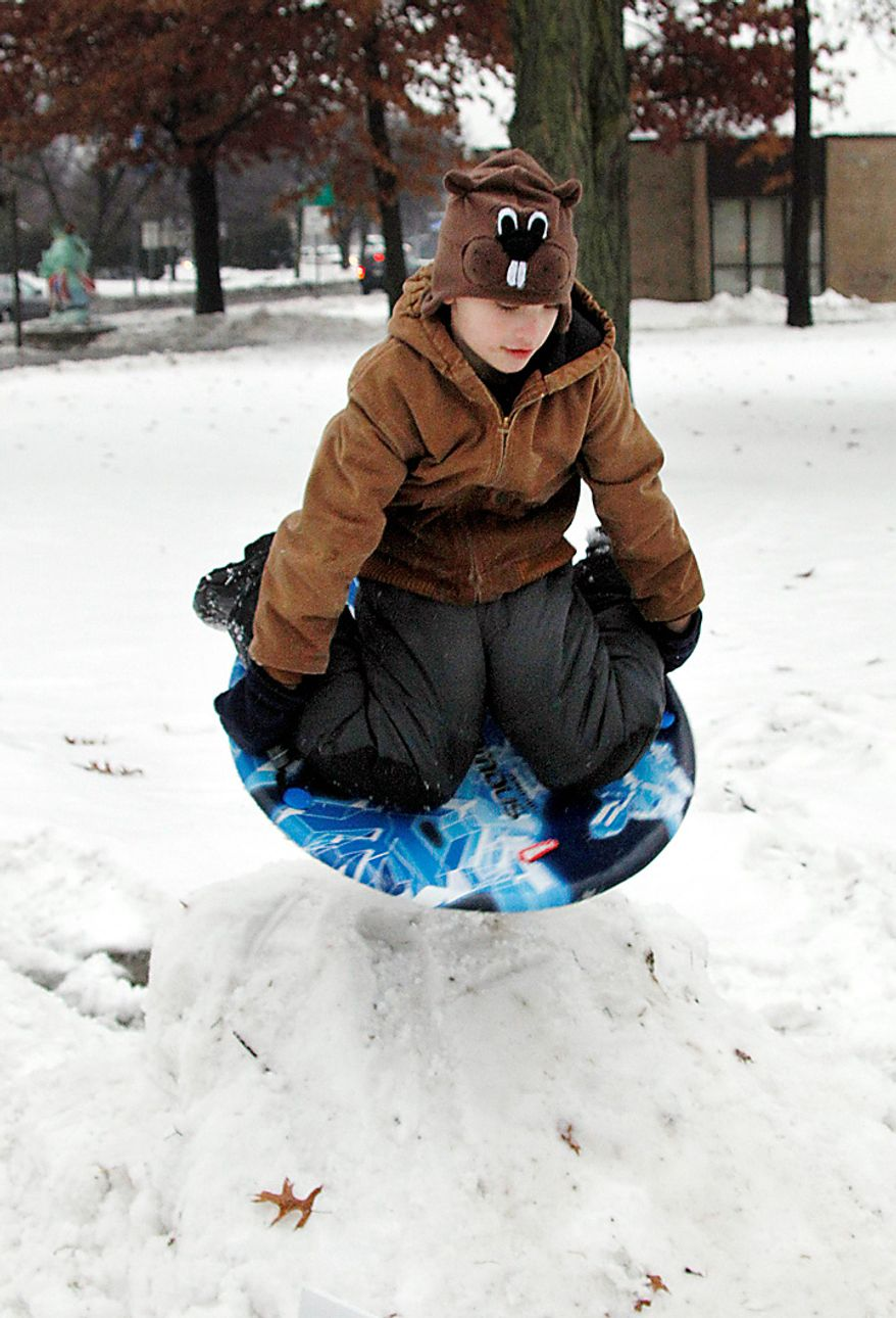 Ethan Watt, 7, wears a groundhog hat as he slides on a saucer down a mound of snow his father piled up for him and his brother at a park in Punxsutawney, Pa., on Tuesday, Feb. 1, 2011. Thousands of people gathered in the small Pennsylvania town in anticipation of the annual gathering at Gobbler's Knob for Groundhog Day. (AP Photo/Keith Srakocic)