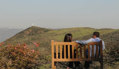 Rachel Duffy of Wisconsin and Matt Kunitz of Los Angeles relax on a park bench overlooking the Santa Susana Mountains at the Ronald Reagan Library and Museum in Simi Valley, Calif. (Garrett Cheen/Special to The Washington Times)