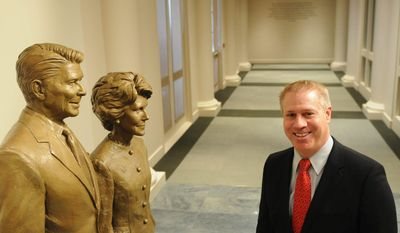 John Heubusch, executive director of the Ronald Reagan Foundation, shows off a new bronze statue of President Reagan and first lady Nancy Reagan. (Garrett Cheen/Special to The Washington Times)
