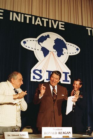Flanked by physicist Edward Teller (left) and Lt. Gen. James A. Abrahamson, director of the Strategic Defense Initiative, President Reagan arrives to address a conference marking the first five years of the SDI program on March 14, 1988, in Washington. (Associated Press)