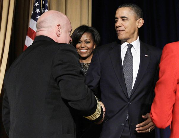 President Obama and first lady Michelle Obama greet astronaut Mark Kelly, husband of wounded Democratic Rep. Gabrielle Giffords, at the National Prayer Breakfast in Washington on Thursday. Failures while in the White House have prompted him to question God's plans for him, the president said. (Associated Press)