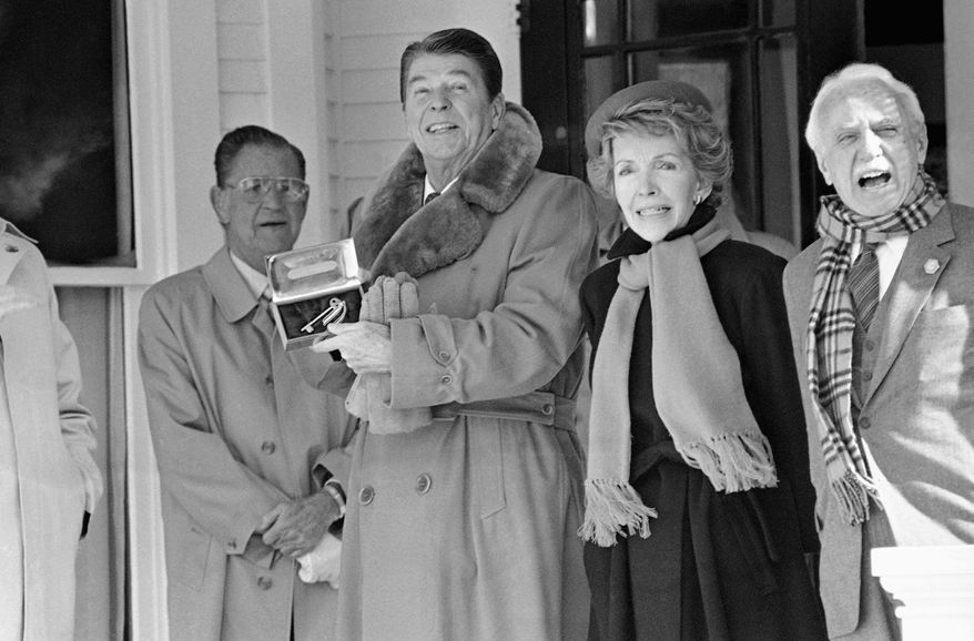 Ronald Reagan, with wife Nancy and brother Neil, holds a gold key to his boyhood home in Dixon, Ill., on Feb. 6, 1984. The home, preserved by a nonprofit foundation, is the most likely candidate for purchase by the National Park Service. (Associated Press)