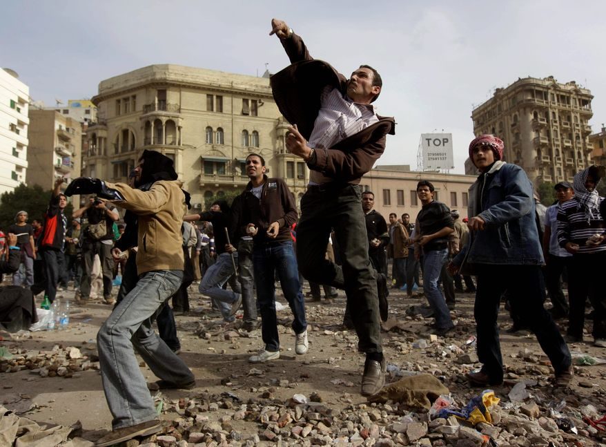 Anti-government protesters throw stones during clashes in Cairo on Thursday. Egypt's prime minister apologized for an attack by government supporters. (Associated Press)