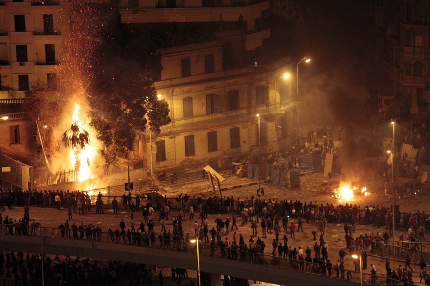 Pro-government demonstrators, bottom, clash with anti-government demonstrators, top right, as a palm tree burns from a firebomb, in Tahrir Square, the center of anti-government demonstrations, in Cairo, Egypt, early Thursday, Feb. 3, 2011. (AP Photo/Lefteris Pitarakis)