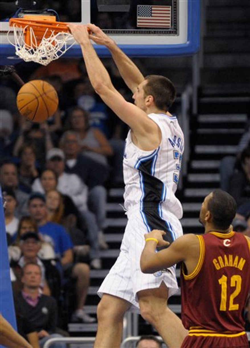Orlando Magic forward Ryan Anderson, left, dunks in front of Cleveland Cavaliers forward Joey Graham during the second half of an NBA basketball game in Orlando, Fla., Sunday, Jan. 30, 2011. The Magic won 103-87.(AP Photo/Phelan M. Ebenhack)