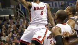 Miami Heat's LeBron James (6) gets past the Orlando Magic defense for two points during the first half of an NBA basketball game in Orlando, Fla., Thursday, Feb. 3, 2011. (AP Photo/John Raoux)