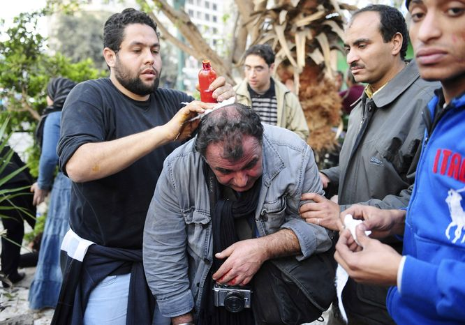 French photojournalist from SIPA Press agency Alfred Yaghobzadeh is being treated by anti-government protesters after being wounded during clashes between pro-government supporters and anti-government protesters, in Cairo's central Tahri