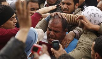 Anti-government demonstrators grab a man they suspect to be a supporter of Egyptian President Hosni Mubarak in Cairo's Tahrir Square, Egypt, Thursday, Feb. 3, 2011. The Egyptian military is taking up positions between anti-government demonstrators and supporters of President Hosni Mubarak. (AP Photo/Victoria Hazou)
