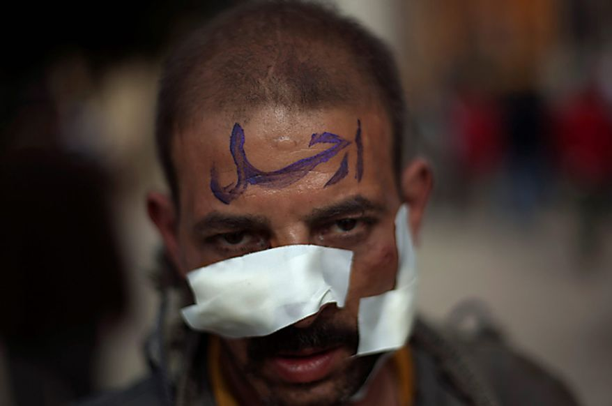 "A wounded Egyptian anti-government protester in Cairo's main square on Thursday, Feb. 3, 2011, wears the Arabic word for ""leave"" painted on his forehead, in support of the protesters' demand for President Hosni Mubarak to leave the office immediately. (AP Photo/Emilio Morenatti)"