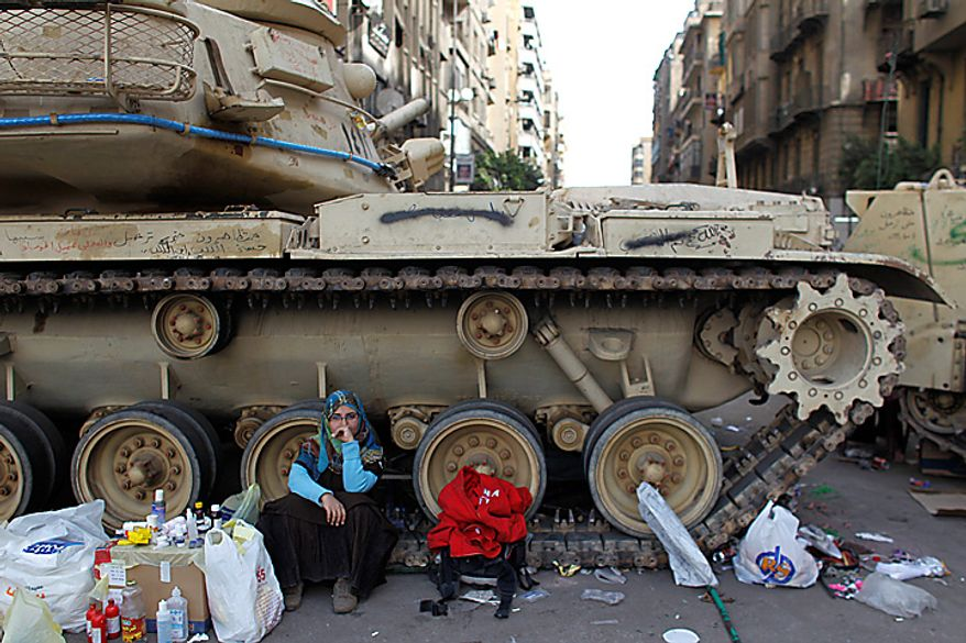 An Egyptian woman sits by a military tank in Cairo's main square Thursday, Feb. 3, 2011, when new clashes heated up again and shots were being fired in the air around Cairo's central Tahrir Square as anti-government protesters pushed back regime supporters. (AP Photo/Tara Todras-Whitehill)