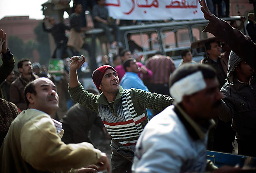 Egyptian anti-government protesters throw stones during clashes in downtown Cairo Thursday, Feb. 3, 2011. New clashes are heating up again and shots are being fired in the air around Cairo's central Tahrir Square as anti-government protesters push back regime supporters. (AP Photo/Emilio Morenatti)